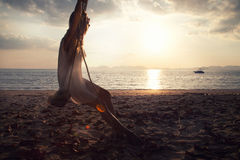 Frau auf dem Strand bei Sonnenuntergang lizenzfreie stockbilder