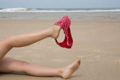 Frau auf dem Strand, der Bikini mit ihrem Bein hält Stockfotografie