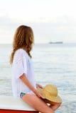 Frau auf dem Strand, der das Schattenbild des Schiffs auf dem Horizont betrachtet Stockfotografie