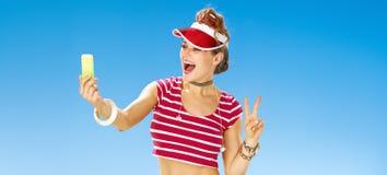 Frau auf dem Strand, der selfie mit Mobiltelefon nimmt und Sieg zeigt Lizenzfreie Stockbilder