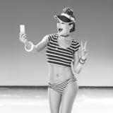 Frau auf dem Strand, der selfie mit Mobiltelefon nimmt und Sieg zeigt Lizenzfreies Stockfoto
