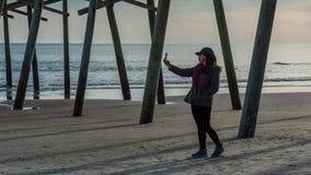 Frau auf dem Strand, der selfie unter Pier mit Ozean im Hintergrund nimmt stockbild
