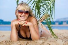 Frau auf dem Strand, der unter die Palme legt Stockfoto