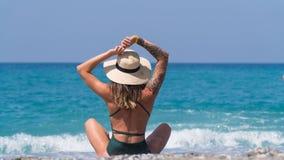 Frau auf dem Strand, der von der Stadthastigen geschäftigkeit stillsteht stockfotos