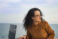 Frau auf dem Strand Eine junge Frau gegen das Meer mit einem Computer- Anstarren in dem Abstand stockfotos