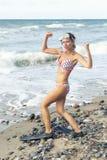 Frau auf dem Strand mit der Schwimmenschutzbrillen- und -flipperaufstellung Stockfoto