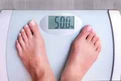 Frau auf dem Wiegen Perfektes Gewicht für eine Frau Gewicht zeigt das Lizenzfreies Stockbild