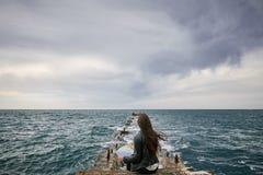 Frau auf der aufpassenden Karte des Piers Lizenzfreies Stockbild