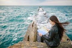 Frau auf der aufpassenden Karte des Piers Stockfotos