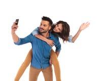 Frau auf der Rückseite des Mannes, während er selfie nimmt Lizenzfreie Stockbilder