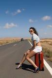 Frau auf der Straße, die auf ihrem Koffer sitzt Stockfotografie