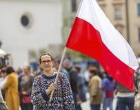 Frau auf der Straße, die eine Flagge der Republik des Polnischen hält lizenzfreie stockfotos