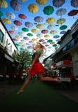 Frau auf der touristischen Dekoration der Straße Stadt, diefarbigen Regenschirm hängt stockbild