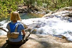 Frau auf die Felsen-Oberseite des Wasserfalls Stockbild