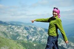 Frau auf die Oberseite des Berges die Richtung zeigend Stockfotografie