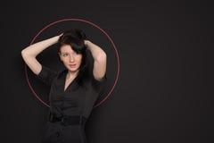 Frau auf dunklem Hintergrund mit einem roten Kreis Lizenzfreies Stockfoto