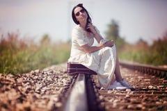 Frau auf einem Bahnretrostil mit einem Koffer Stockbild