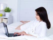Frau auf einem Bett mit Laptop Lizenzfreies Stockbild