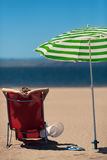 Frau auf einem deckchair am Strand Stockbild