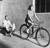 Frau auf einem Fahrrad, das einen gewachsenen Mann auf einem Spielzeugdreirad zieht (alle dargestellten Personen sind nicht länge Stockbild
