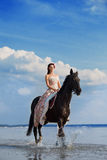 Frau auf einem Pferd durch das Meer stockbilder