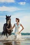 Frau auf einem Pferd durch das Meer stockfotos