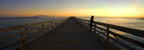 Frau auf einem Pier während des Sonnenuntergangs Lizenzfreie Stockfotografie
