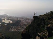 Frau auf einem Rand eines Berges Talansicht genießend Lizenzfreies Stockfoto