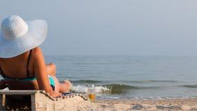 Frau auf einem Ruhesessel im Hut Lizenzfreies Stockfoto
