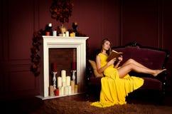 Frau auf einem Sofa mit einem Buch lizenzfreies stockfoto
