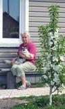 Frau auf einem Sommerwohnsitz mit einer Katze auf Händen Lizenzfreie Stockfotos