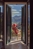 Frau auf einem Stuhl auf dem Balkon Lizenzfreies Stockfoto
