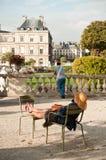 Frau auf einem Stuhl in Luxemburg-Gärten in Paris, Stockfotografie