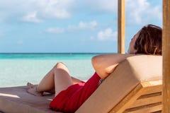 Frau auf einem sunchair, welches die idyllische Ansicht in einen tropischen Standort sich entspannt und schaut Klares T?rkiswasse lizenzfreies stockfoto