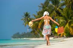 Frau auf einem tropischen Strand mit orange Tasche Lizenzfreie Stockfotos