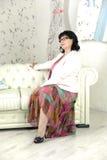 Frau auf einem weißen Sofa Lizenzfreie Stockfotos