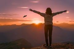 Frau auf einen Berg bei Sonnenuntergang schaut Adler Stockfotografie