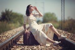 Frau auf einer Eisenbahn, die auf einem Koffer sitzt Stockbilder