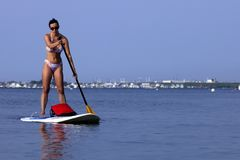 Frau auf einer Stellung herauf Paddleboard-SUP lizenzfreie stockbilder