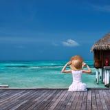 Frau auf einer Strandanlegestelle bei Malediven stockfotografie