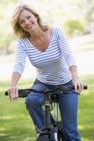 Frau auf Fahrrad draußen lächelnd Stockfotografie