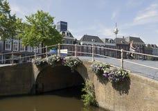 Frau auf Fahrrad führt bunte Blumen auf Brücke in der Mitte von Stockfoto