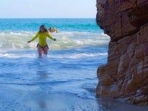 Frau auf felsigem Strand Stockbild