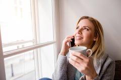 Frau auf Fensterbrett mit dem Smartphone, der Telefonanruf macht Lizenzfreie Stockbilder