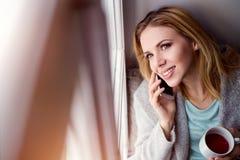 Frau auf Fensterbrett mit dem Smartphone, der Telefonanruf macht Stockfoto
