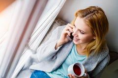 Frau auf Fensterbrett mit dem Smartphone, der Telefonanruf macht Lizenzfreies Stockfoto