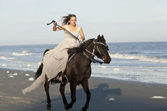 Frau auf galoppierendem Pferd auf Strand stockfoto