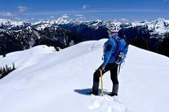 Frau auf Gebirgsoberseite bedeckt mit Schnee Lizenzfreie Stockfotos