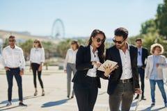 Frau auf Geschäftsreise mit den Mitarbeitern, die auf Tablette zeigen Stockfotografie
