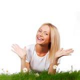 Frau auf Gras mit Blumen Lizenzfreie Stockfotos